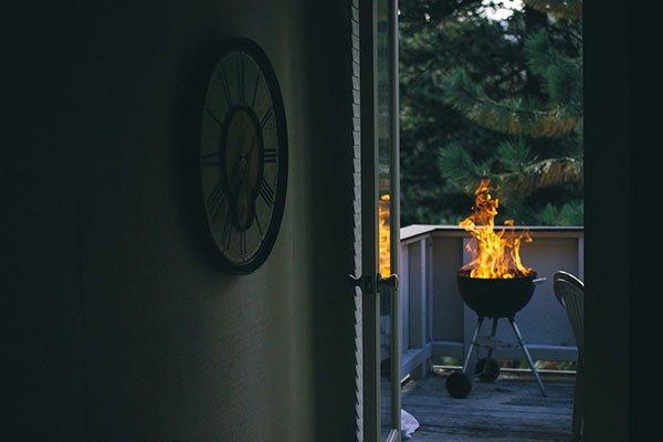 През отворена врата на балкона се вижда подвижно барбекю.