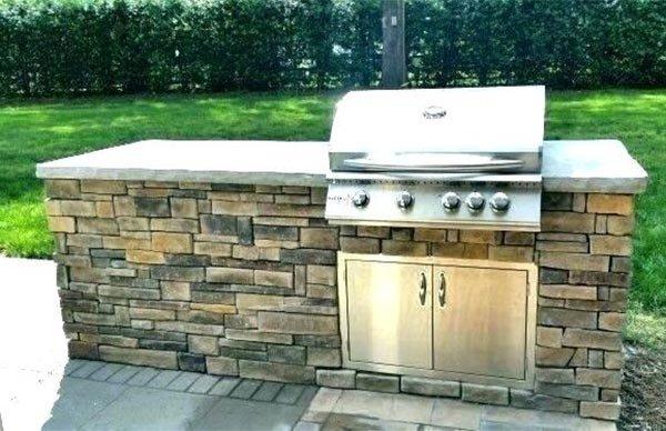 Метално барбекю, вградено в каменна стена в комбинация с вграден метален шкаф.