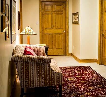 Антре със светъл керамичен под, мек килим и диван двойка.