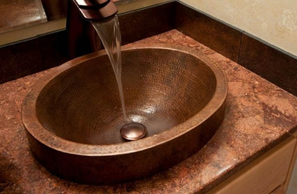 Медна мивка върху каменен плот.